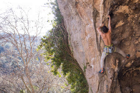 A climber climbs a rock, a man trains strength and  overcoming the fear of heights