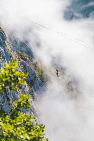 a man walks along a stretched sling high above the clouds. highliner catches the balance on a long and high sling pull in a canyon. Extreme sports in Bosnia and Herzagovina