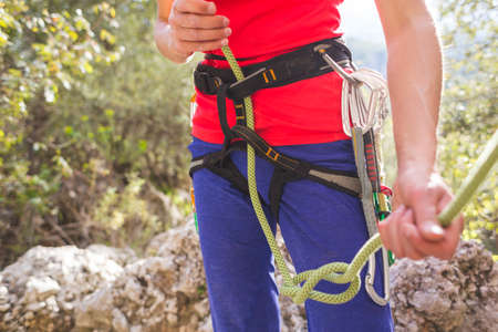 A girl rock climber ties herself with a rope to the harness for safe climbing in the mountains. safety in sports. preparation for rock climbing. doing sports on the street.