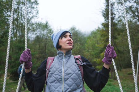 A girl sits on a swing in the forest, a woman travels through picturesque places, a brunette in a hat and mittens on a wooden swing.