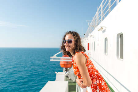 happy girl in a red sundress floats on the ship. summer ocean cruise. summer rest. 版權商用圖片