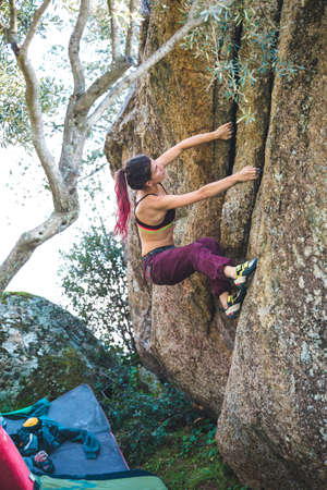 Bouldering on natural terrain, a strong woman climbs a boulder, a girl goes in for sports in nature, an effort to overcome