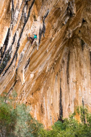 A woman climbs a rock on a colony. A slender girl overcomes a difficult climbing route. A climber trains on natural terrain. Fitness in nature. Extreme hobby. ... rock climbing in Turkey Datca region. 版權商用圖片