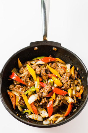 skillet: Stir fried beef steak with colorful pepper and onion in a pan on isolated white background.