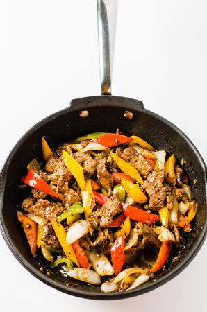 pepe nero: Mescolare bistecca di manzo fritto con pepe colorato e cipolla in una padella isolato backgroun bianco. Archivio Fotografico