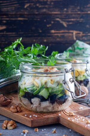 Fresh salad with boiled chicken breast, prune, egg and fresh cucumber, selective focus