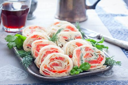 Lavash roll with red fish and cheese on a metal dish, horizontal