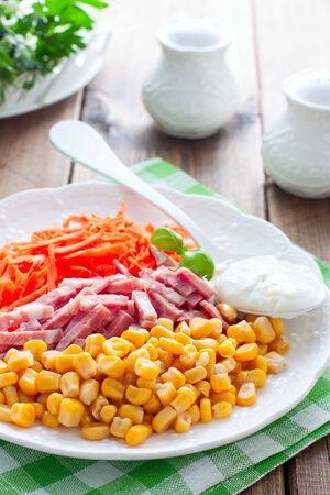 Salad with fresh carrots, sausage and corn on a white plate, selective focus