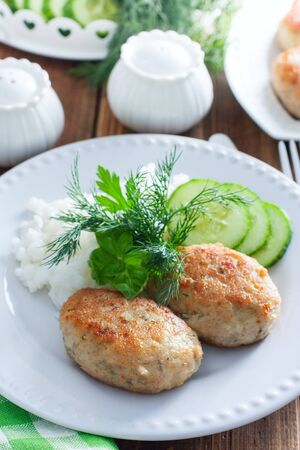 Fried fish cakes on a white plate with rice, selective focus