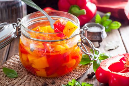 Fermented multicolored bell peppers in a glass jar, selective focus