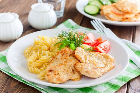 Chicken in batter with pasta on a white plate, selective focus Фото со стока