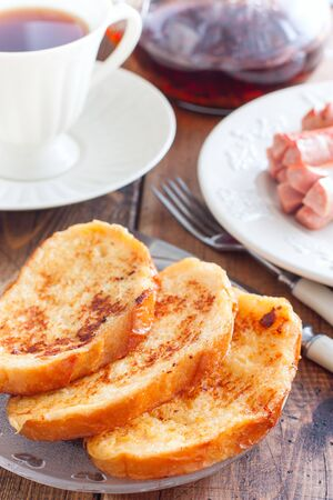 Toasted white bread on a plate on a wooden table, selective focus