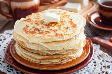 Homemade thick pancakes stacked on a plate, selective focus