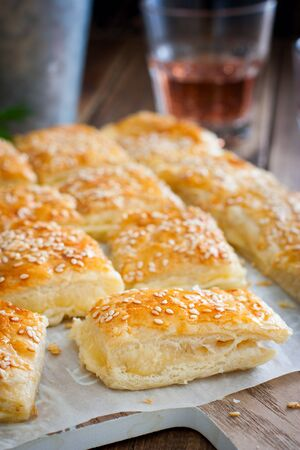 Puff pastry pie with cheese, sprinkled with sesame seeds, selective focus Reklamní fotografie