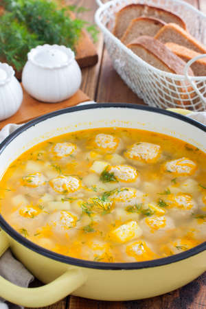 Potato soup with meatballs in an enameled pan on a wooden table, selective focus Imagens