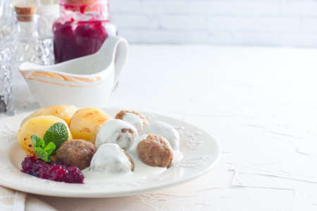 Swedish meatballs with cream sauce, boiled potatoes and cranberry jam, horizontal, copy space
