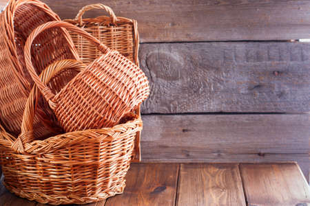 Woven empty baskets from natural handmade vines for mushrooms, handicrafts, storage, walks, picnic on a wooden table, copy space 版權商用圖片