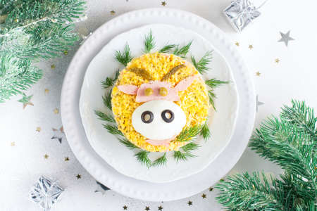 Festive salad with decoration in the form of a bull's face symbol of the year, idea for a festive christmas table and children, top view, horizontal Stock Photo