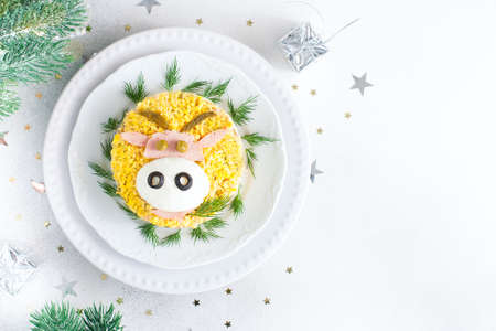 Festive salad with decoration in the form of a bull's face as a symbol of the year, idea for a festive Christmas table and children, top view, horizontal, place for text or recipe Stock Photo
