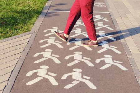 A man crosses a bike path in a park at a pedestrian crossing