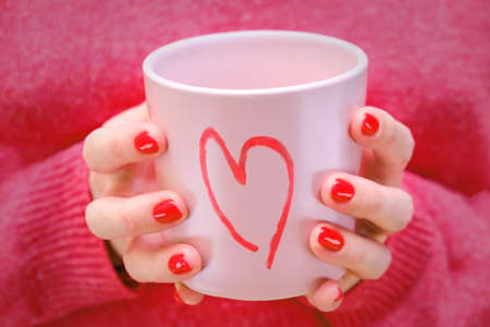 A woman holds a pink cup with a painted heart. The girl in the red sweater with a romantic mug.