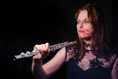 Halloween musician with flute on black background, copy space. Evil woman with lipstick smeared on her face, closeup portrait