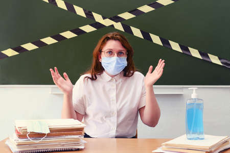 A teacher in a medical mask throws up his hands in dismay. Concept of problems with learning during coronavirus quarantine. Classroom safety during lessons in the coronavirus epidemic Reklamní fotografie