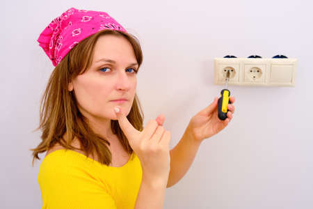 A woman threatens a finger while repairing an electrical outlet. Warning for live electrical repairs Banco de Imagens
