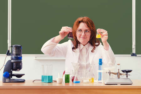 Chemistry teacher looks at reagent bubbles while sitting at a desk at school. Chemistry lesson with colorful flasks, test tubes and a microscope, copy space. Foto de archivo