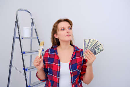 A woman in a plaid shirt and money to renovate a new home. Dollars for the decoration of the built apartment. 写真素材