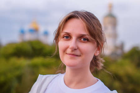 Woman on the background of the Christian Church. The girl in the evening next to the domes of the temple. Female portrait on the background of the Church.