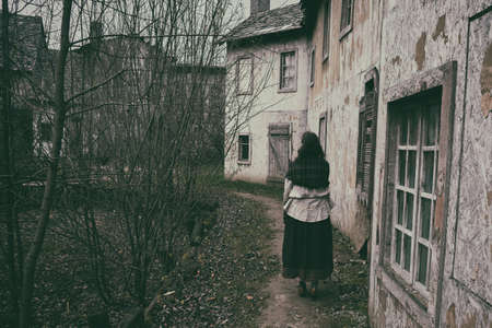 A woman with a shawl on her shoulders walks along the path of an old sad city in medieval Europe