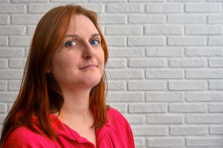 Portrait of a young redhead woman in red clothes on a background of a white brick wall
