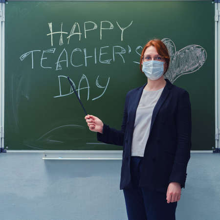 """Learning problems concept during quarantine coronavirus. Young woman in a medical mask and with a pointer by the blackboard with the text """"Happy Teacher's Day."""""""