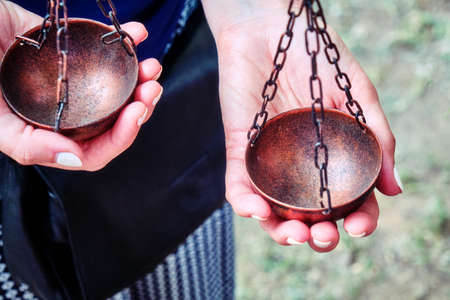 A woman holds a bowl of vintage weights. Libra Themis in the hands of a young girl, lifestyle.