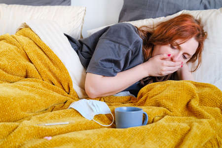 Young woman coughing while lying on bed with a cup of tea