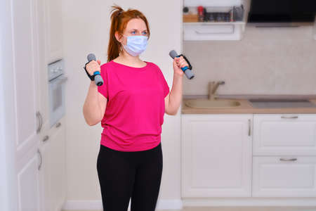 A girl lifts dumbbells against the background of home cooking, the concept of sports in quarantine. The woman is engaged in fitness during the isolation because of the infection of coronavirus