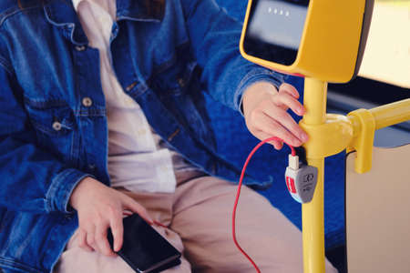 A man connects a phone wire on the bus. Mobile phone charger with usb in public transportand stop button Zdjęcie Seryjne
