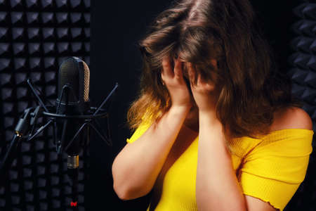 Woman in the recording Studio covered her face with her hands. Problems with fatigue, loss of voice have singers and vocalists, black background.