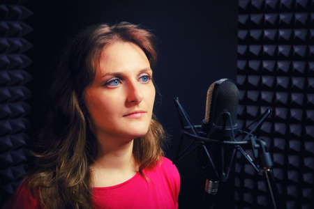 Woman in the red dress is behind the microphone. The singer looks forward to the recording Studio. Girl with blue eyes on a black background in misic studio. Stock Photo