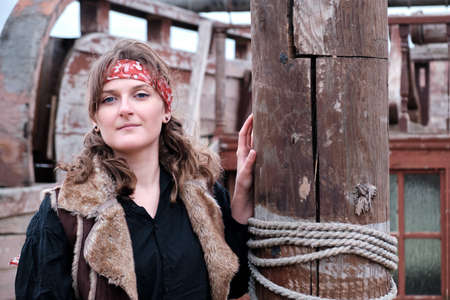 Portrait of a pirate woman next to the mast of an old wooden sailing ship