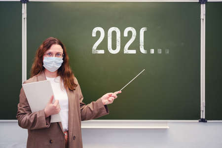 Teacher in a medical mask at the blackboard with an indeterminate year of the end of quarantine. Concept of problems at school during the coronavirus epidemic