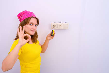 Woman shows gesture-all okay repairing socket, copy space. Compliance with safety regulations when working with electricity.