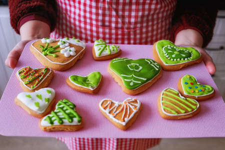 Girl holding a tray of gingerbread. In hands of women baking handmade. Painted gingerbread in form of hearts and flowers. Green and yellow cookies decorated with glaze