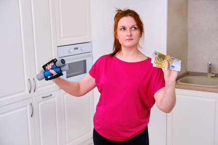 A woman is holding money in euros doubting about buying equipment for fitness training. The concept of acquiring sports equipment on isolation at the quarantine coronavirus