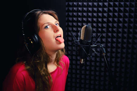 A young woman shows her tongue at the recording Studio. The singer in the headphones was tired of writing songs. Music Studio, microphone, black background.