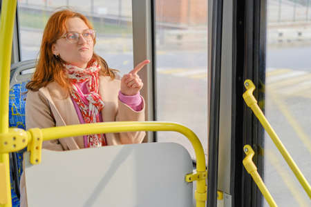 A red-haired woman rides a bus and points her finger at the road
