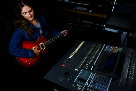 Female guitarist sitting at the mixing console in the recording studio. Woman with a red electric guitar records a song at the music studio.