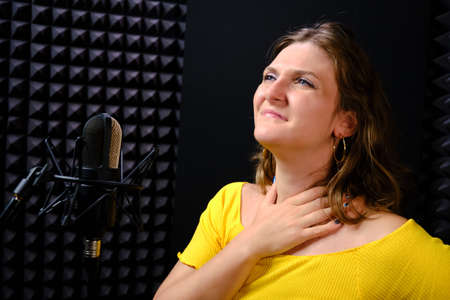 A young woman holding her throat near the microphone, black background. The voice of the singer when recording a song in the music Studio. Voice failure, hoarseness, pain in the vocal cords.