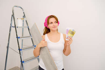 A satisfied worker with money in her hands on the background of a renovated apartment. Money for the repair of new housing. 版權商用圖片